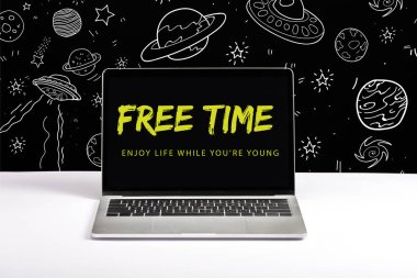 laptop on table with enjoy life while you are young and free time lettering on screen with white galaxy illustration on black