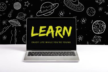 laptop on table with enjoy life while you are young and learn lettering on screen with white space illustration on black