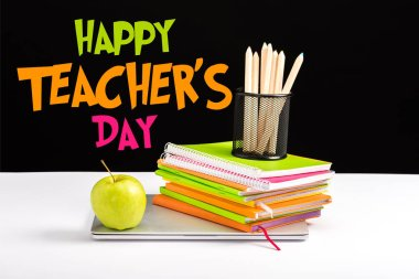 closed laptop, green apple, notebooks and color pencils on desk with happy teachers day lettering on black
