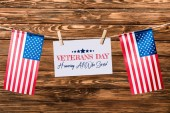 Fotografie card with veterans day lettering hanging on string with pins and american flags on wooden background