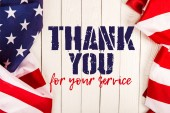 Fotografie top view of american flags and thank you for your service lettering on white wooden surface