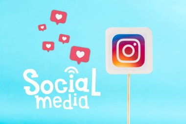 card with instagram logo and social media lettering with heart icons isolated on blue