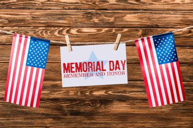 Card with memorial day lettering hanging on string with pins and american flags on wooden background stock vector