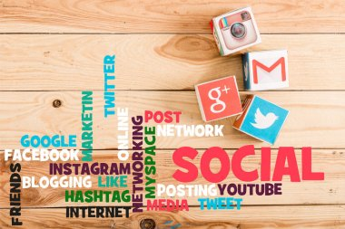 top view of blocks with google plus, gmail, instagram and twitter logo on wooden table with social media illustration