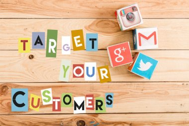 top view of cubes with google plus, gmail, instagram and twitter logo on wooden table with target your customers lettering