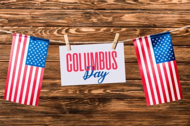 card with Columbus day lettering hanging on string with pins and american flags on wooden background