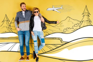 happy woman showing thumb up and hugging boyfriend with mountains and airplane illustration on yellow background