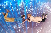 Fotografia elegant couple holding hands and flying together with space illustration and sparkles on background