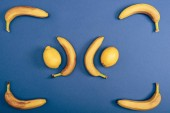 Top view of juicy and fresh lemons with yellow bananas on blue background