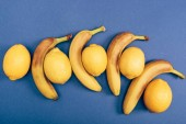 Top view of bright and yellow lemons with bananas on blue background