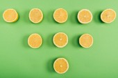Top view of food composition of juicy and fresh cut lemons on colorful green background