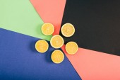 Fotografie Top view of bright yellow cut lemons on multicolored black blue coral green background