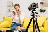 mosolygó szépség blogger tükörrel dekoratív kozmetikumok előtt videó kamera