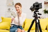 szelektív középpontjában mosolygó szépség blogger tükör segítségével dekoratív kozmetikumok előtt videokamerát
