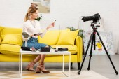 Photo beauty blogger doing makeup in front of video camera at home