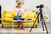 Photo smiling beauty blogger with mirror and decorative cosmetics sitting on sofa near video camera