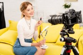 Photo beauty blogger holding lipstick and mirror in front of video camera