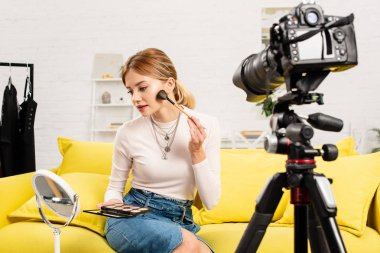 Beauty blogger doing makeup in front of video camera at home stock vector