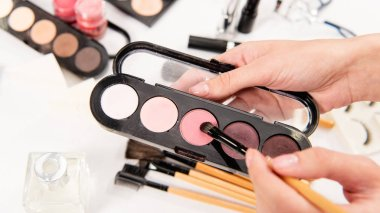 cropped view of woman holding eye shadows and cosmetic brush