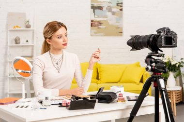 beauty blogger sitting at table with decorative cosmetics in front of video camera