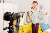 mosolygó blogger gazdaság bevásárló táskák előtt videokamerát otthon