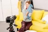 Blogger ül kanapén csukott szemmel, és bemutatja ruhát előtt videokamerával
