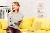 okouzlující nezávislý pracovník v módních náušnicemi, které sedí na žluté pohovce a používají smartphone doma
