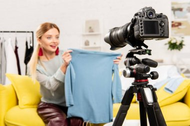 Selective focus of smiling blogger sitting on sofa and showing clothes in front of video camera stock vector
