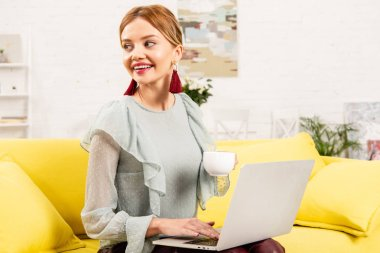 Smiling freelancer sitting on yellow sofa with cup of coffee and using laptop stock vector