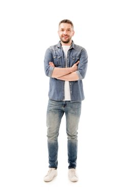 Full length view of smiling bearded man in jeans standing with crossed arms isolated on white stock vector