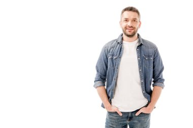 front view of smiling bearded man in denim shirt standing with hands in pockets isolated on white