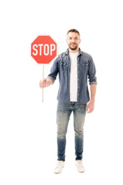 Full length view of smiling bearded man man in denim shirt holding stop sign isolated on white stock vector