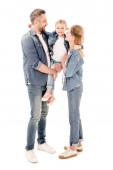 Plná délka pohled na šťastné rodiče v džínách, držící dceru izolovanou na bílém