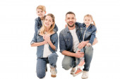 happy family in jeans embracing and smiling isolated on white