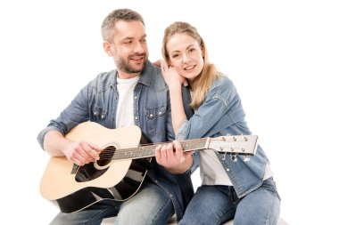 smiling man in jeans playing acoustic guitar for wife isolated on white
