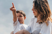 serious boy pointing with finger near attractive mother