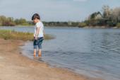 roztomilý chlapec stojící v jezeře u mokrého písku