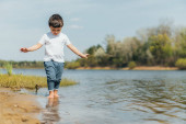 Selektiver Fokus des niedlichen Jungen, der im Teich steht