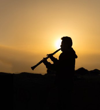 An unidentified man plays clarinet at sunset on the beach in Istanbul,Turkey.18 April 2015