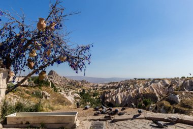 Guvercinlik Valley and Fairy tale chimneys on background of blue sky in Turkey.The great tourist attraction of Cappadocia one of the best places to fly with hot air balloons. Goreme, Cappadocia, Turkey.