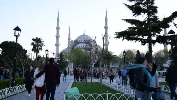 Unidentified people walk in Sultanahmet park with view of Sultanahmet Mosque or Blue Mosque in Istanbul, Turkey. 21 April, 2018.