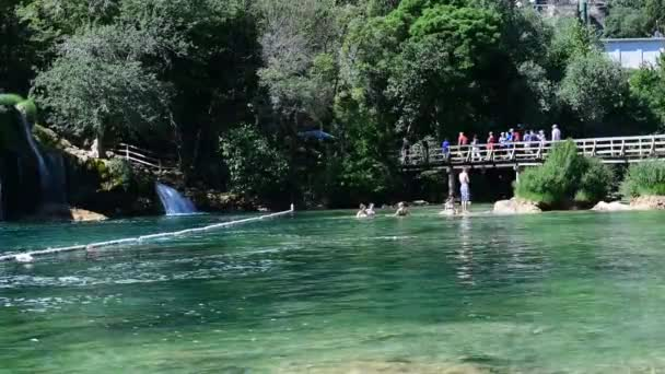 Tourists walk over bridge in Krka National Park one of the most famous national parks and visited by many tourists: Skradinski Buk, KRKA NATIONAL PARK, CROATIA, MAY 27, 2017.