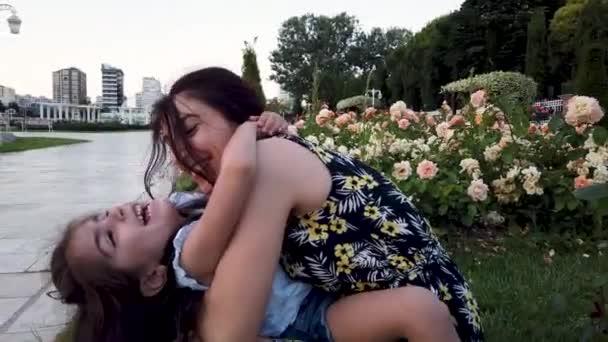 Mutter und Tochter umarmen sich und haben Spaß im Park