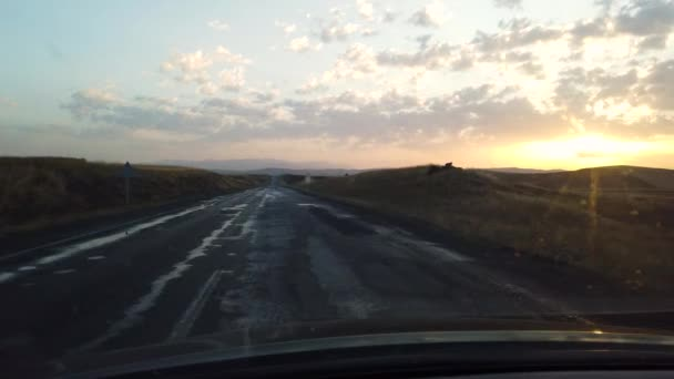 Pohled z vnitřního vozu na prázdnou kopcovitý silnici vedoucí k čáře obzoru při západu slunce nebo východu slunce