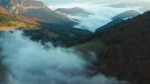 Ranní mlha se valí mezi horami nad stromy zabarvenými v podzimních barvách