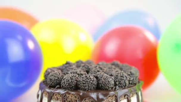 torta di compleanno con palloncini in background