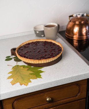 homemade dessert of cherry tart, on a brown wooden board, dry leafs autumn composition, kitchen interiour