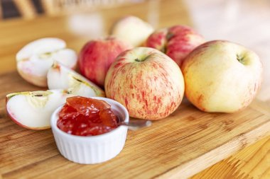 Harvest beautiful apples with red barrels and jam from them. Still life on a wooden board on the table.