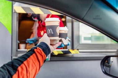 Moscow, Russia, 30/05/2020: A man takes an order from a delivery window to McDonald's. Drive thru.