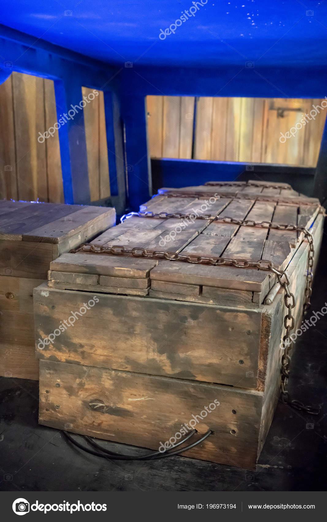 cercueil bois ancien avec chaînes métalliques rouillées nouée autour